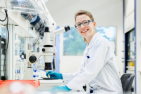 Researcher in white lab coat smiles while sitting in lab