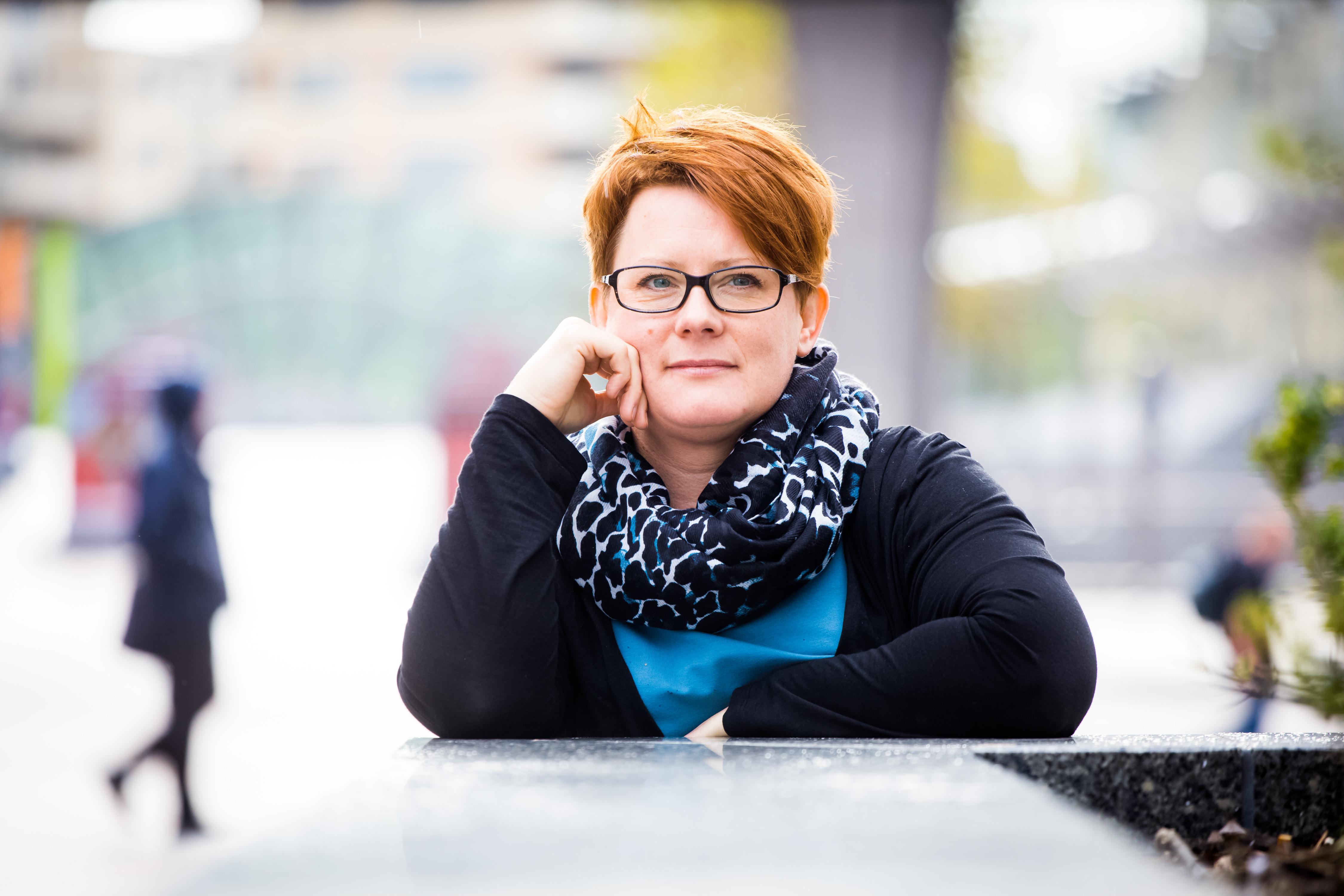 Patient in glasses leans against ledge